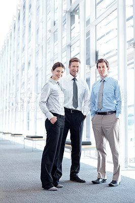 Buy stock photo Three businesspeople smiling at the camera - full length