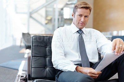 Buy stock photo A handsome businessman holding paperwork while looking at the camera