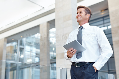 Buy stock photo A handsome businessman smiling while holding his digital tablet