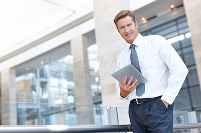 Buy stock photo A handsome businessman holding a digital tablet