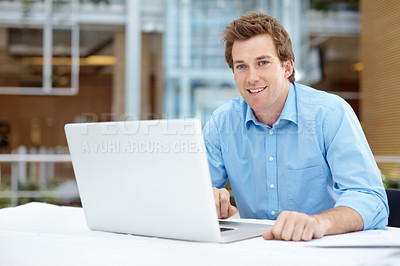 Buy stock photo A handsome young businessman smiling at the camera while working on his laptop