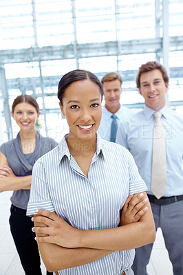 Buy stock photo Pretty young businesswoman smiling with a team behind her