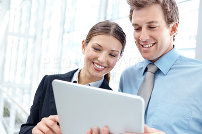 Buy stock photo Young businesspeople sharing a tablet together