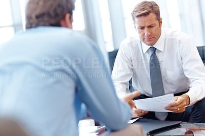 Buy stock photo Mature businessman using a tablet during a meeting with a younger businessman