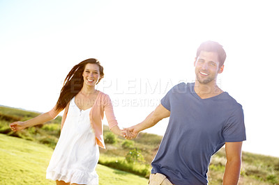 Buy stock photo A happy couple holding hands and running through a field