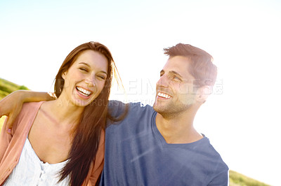 Buy stock photo A laughing couple walking in the sunshine of a field
