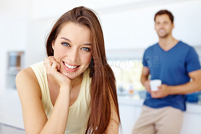 Buy stock photo Closeup portrait of a young woman in her kitchen with her husband standing in the background