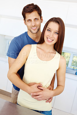 Buy stock photo Portrait of a good-looking young couple standing at a counter in their kitchen and embracing