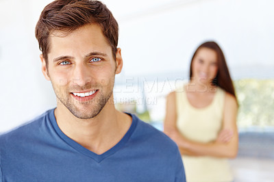 Buy stock photo Close up portrait of a young man standing in his kitchen with his wife in the background