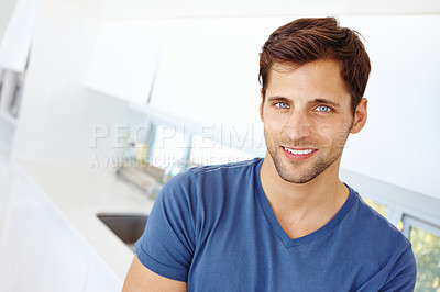 Buy stock photo Portrait of a handsome young man standing in his kitchen and smiling at the camera