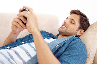 Buy stock photo Shot of a handsome young man lying on a a sofa and sending text messages