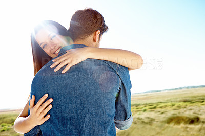 Buy stock photo Portrait of a man with his back to the camera being hugged by his wife on a sunny day outside
