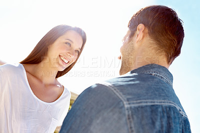 Buy stock photo Low angle shot of a two young people staring lovingly into each other's eyes while out on a sunny day