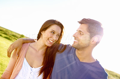 Buy stock photo Shot of a young man with his arm around his girlfriend while enjoying a day out