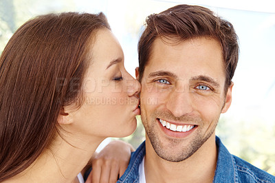 Buy stock photo Cute young woman kissing her boyfriend on the cheek