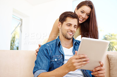 Buy stock photo Cute young couple using a digital tablet together at home