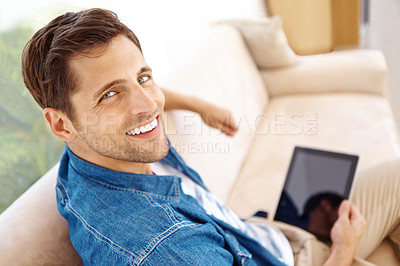 Buy stock photo Handsome young man using his tablet while on the sofa at home