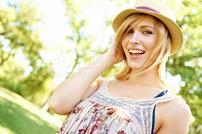 Buy stock photo Portrait of a happy blonde holding on to her hat and smiling with an outdoors copyspace