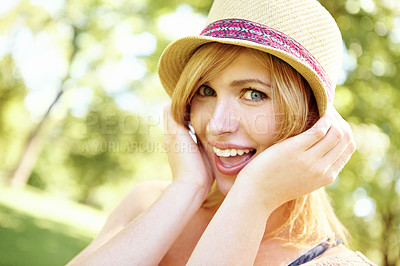 Buy stock photo Portrait of a fun blonde holding on to her hat in the outdoors with copyspace