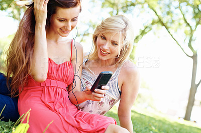 Buy stock photo Girl friends listening to music on their phone and sitting in the park bonding