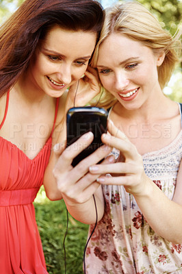 Buy stock photo Girl friends sitting in the park listening to the music on their cell-phone