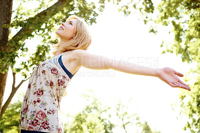 Buy stock photo Side view of a beautiful young woman standing in a park with her arms outstretched