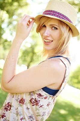 Buy stock photo A side view of a beautiful young woman looking at the camera and holding the edge of her sunhat