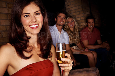 Buy stock photo A beautiful woman holding a glass of champagne with friends sitting in the background