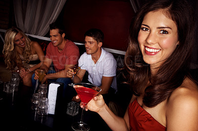 Buy stock photo Portrait of an attractive woman drinking a martini with her friends sitting behind her