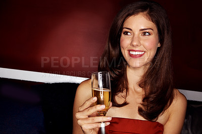 Buy stock photo Shot of an attractive young woman drinking champagne while sitting in a night club