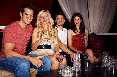 Buy stock photo Portrait of four good-looking young people sitting in a nightclub together and drinking cocktails