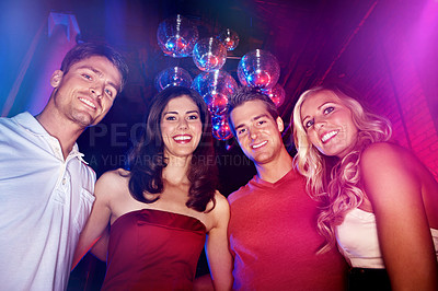 Buy stock photo Low-angle portrait of four young friends out on a night on the town