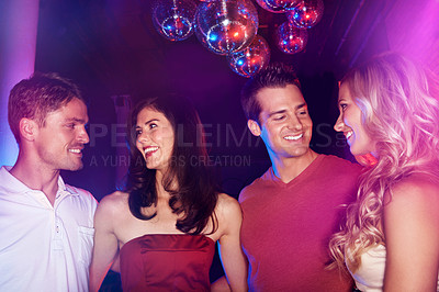 Buy stock photo Shot of four good-looking young people standing in a nightclub together under some disco balls