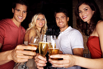 Buy stock photo Portrait of four young people toasting each other with champagne in a night club