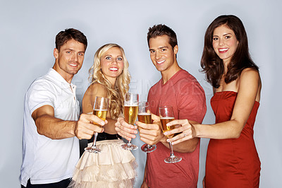 Buy stock photo Studio shot of a group of young people toasting with champagne