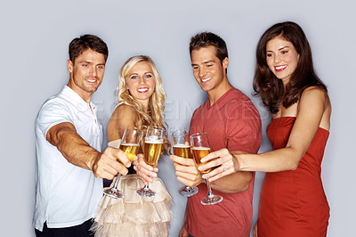 Buy stock photo Studio portrait of a group of young people toasting with champagne