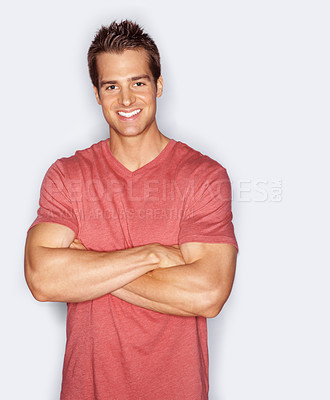 Buy stock photo Studio portrait of a fit young man standing with his arms folded