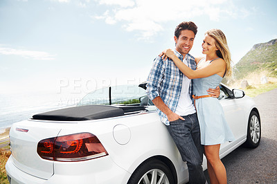 Buy stock photo A young couple standing outside their car while on a roadtrip