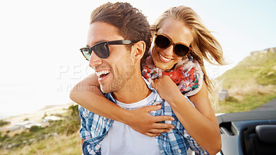 Buy stock photo An affectionate young couple enjoying the views while on a roadtrip