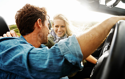 Buy stock photo A handsome young man driving his car with his girlfriend while on a roadtrip