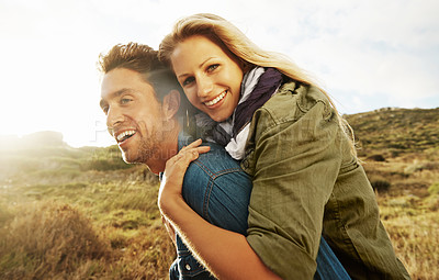 Buy stock photo An attractive young woman embracing her boyfriend from behind while outdoors