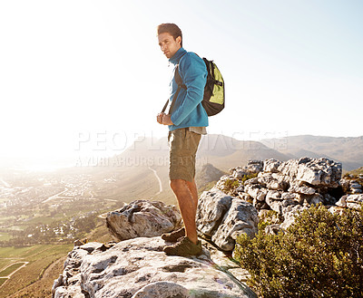 Buy stock photo Handsome hiker standing at the top of a mountain