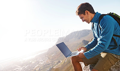 Buy stock photo Handsome hiker using a laptop at the top of a mountain