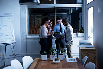 Buy stock photo Shot of a group of businesspeople working with a digital tablet late at night. Real life businesspeople shot on location. Since these locations are the real thing, and not shot in an