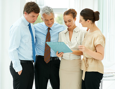 Buy stock photo Portrait of business team going through a file and discussing with each other