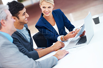 Buy stock photo A gorgeous young businesswoman pointing something out to her colleagues
