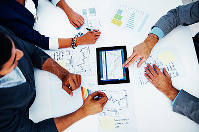 Buy stock photo Cropped high-angle image of a group of businesspeople working together on a digital tablet