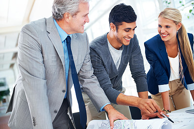 Buy stock photo A group of architects looking at plans together