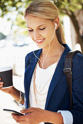 Buy stock photo A gorgeous young businesswoman choosing a song from her mp3 player while standing outside with a cup of coffee