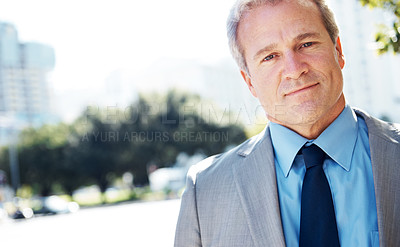 Buy stock photo A handsome businessman standing outside while looking at the camera